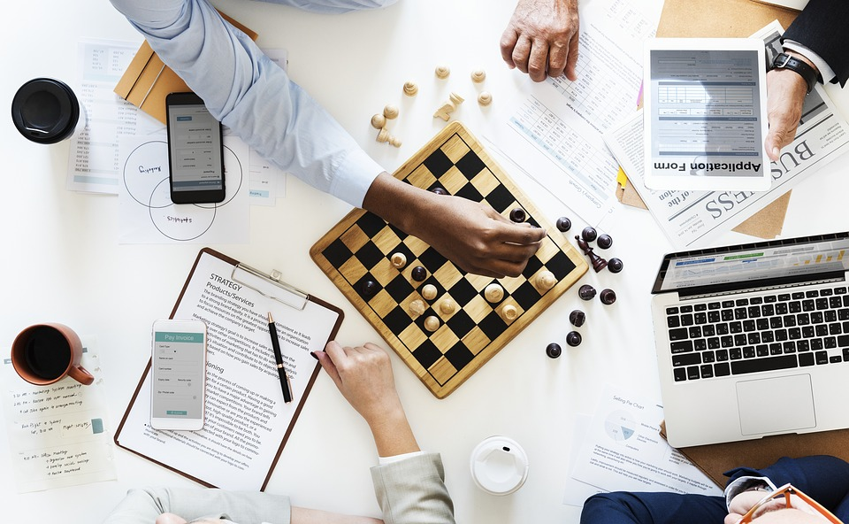 Coworkers playing chess stock photo.